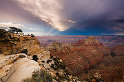 Beams of sunlight known as Anti-Crespecular Rays pass over the North Rim of the Grand Canyon towards the Painted Desert.