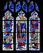 Saint Louis, King Louis IX of France, born in Poissy in 1214, with allegorical figures of Peace and Labour, stained glass window in the Chapelle St Barthelemy in the Collegiale Notre-Dame de Poissy, a catholic parish church founded c. 1016 by Robert the Pious and rebuilt 1130-60 in late Romanesque and early Gothic styles, in Poissy, Yvelines, France. The Collegiate Church of Our Lady of Poissy was listed as a Historic Monument in 1840. Picture by Manuel Cohen