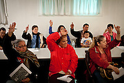 Residents vote on resolving issues with community alleyways during a meeting of the Parklawn United Neighbors in Modesto, Calif., March 1, 2012.