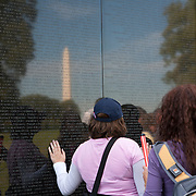 The Vietnam Veterans Memorial in Washington, D.C. honors members of the U.S. armed forces who fought in the Vietnam War, and those who died during service in Vietnam/South East Asia, and the Missing In Action from the War. Visitors touch, caress and rub names on the onto papers. The Washington Memorial can be seen in the background. The memorial was designed by American architect Maya Lin<br />
