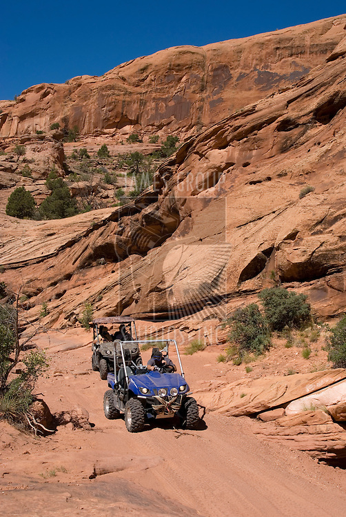 2 side-by-side ATVs coming down a dirt trail.
