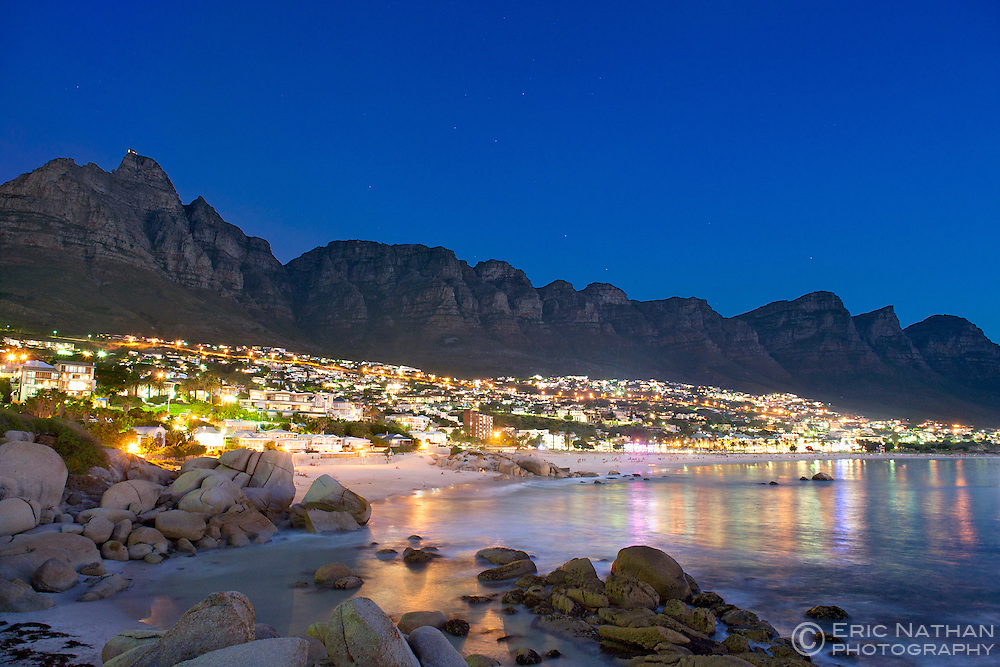 Moonlit view of Camps Bay, Camps Bay beach and the Twelve Apostles mountains in Cape Town, South Africa.
