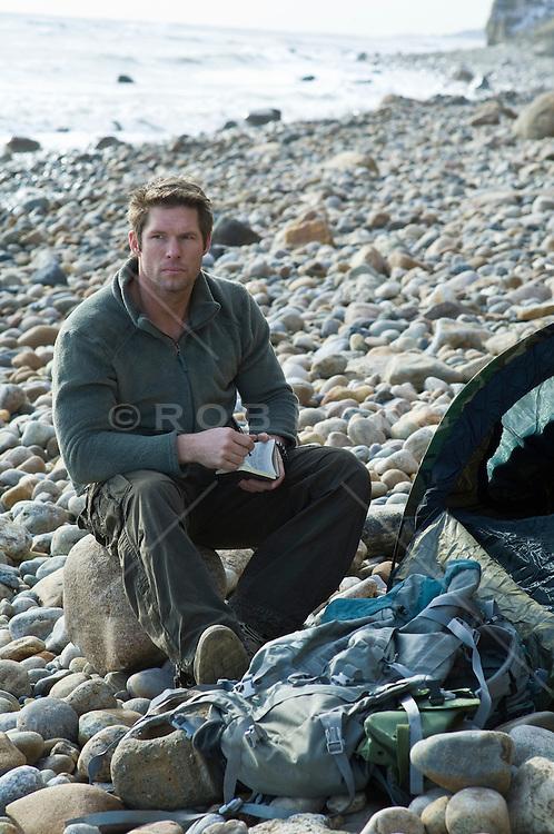 man camping on a rocky beach in Montauk, NY