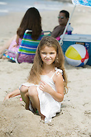 Portrait of girl on beach, parents in background