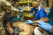 Transported by U.S. Army medevac helicopter, a multi-national team of doctors and nurses treat a battlefield casualty at Kandahar Airfield Hospital, Kandahar Province, Afghanistan.
