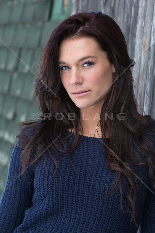portrait of a beautiful woman with black hair and blue eyes outdoors