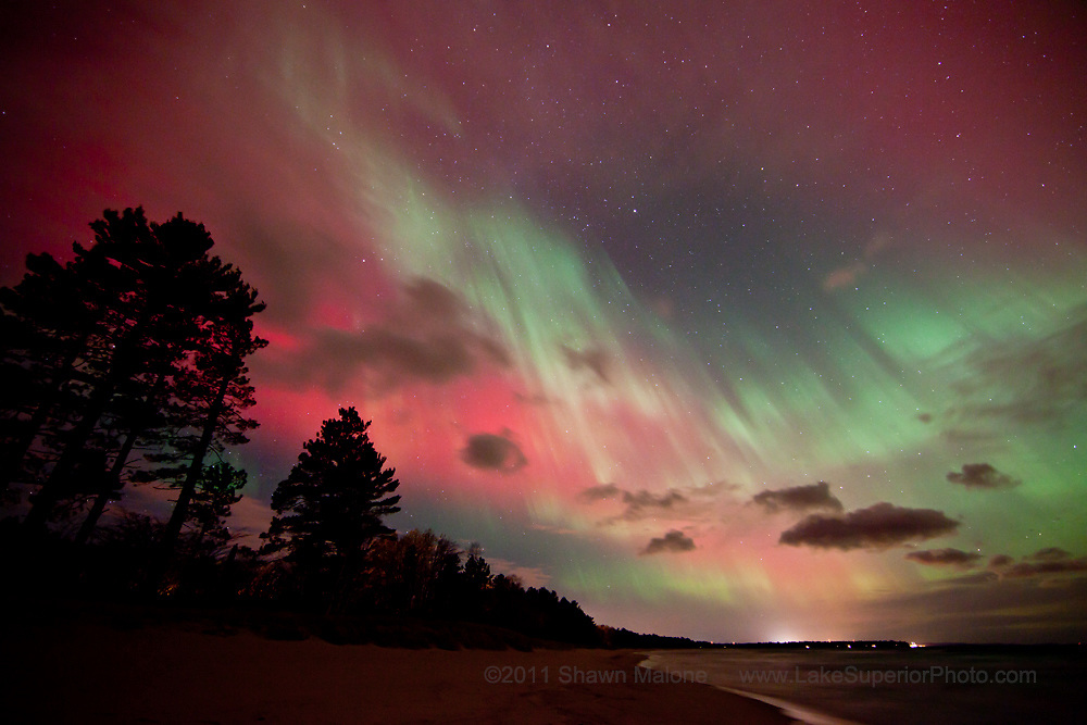 Jaw dropping multi colored curtain visible overhead and to the south over Lake Superior, Marquette MI. Camera is pointed west, glow of Mqt is visible on tree line. Featured on National Geographic Daily News 10/24/2011,  National Geographic's most popular 10/27/2011, Spaceweather.com 10/24/2011