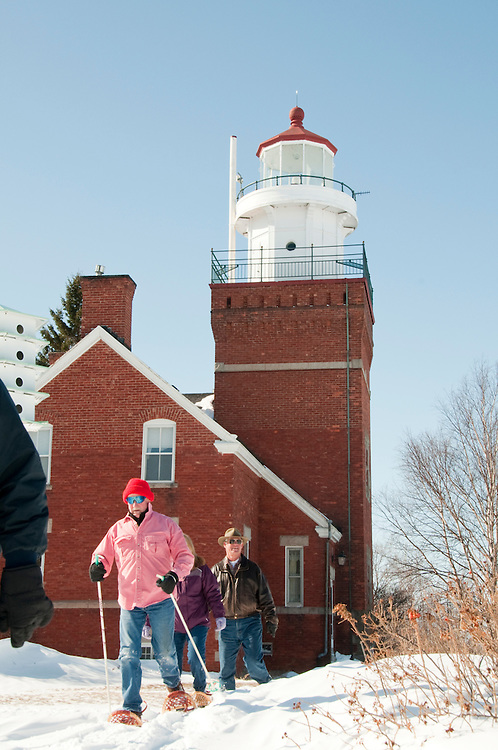 Guests of the Big Bay Lighthouse Inn snowshoe on the lighthouse grounds in Big Bay Michigan.