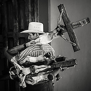 Mexican man carrying sculptures of the crusified christ in San christobal de las Casas in Mexico. For more mexico images see www.aurora.is