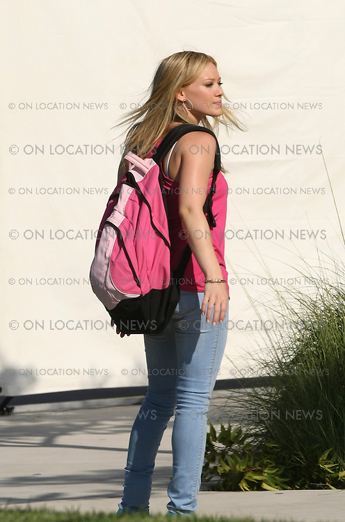 LOS ANGELES, CALIFORNIA - TUESDAY 29th JULY 2008 ***EXCLUSIVE*** Hilary Duff filming High School scenes for 'Stay Cool'. Hilary appears to have gained some weight for her role. While on the set Duff seemed to be irritated by the work of the hair and make up artist. Hilary was also was seen yawning as well as having what appeared to be digestive problems. At one point Duff tried to manage carrying her iPhone, a bottled water, and a Diet Coke. After filming scenes walking around a high school campus Duff changed wardrobe for a Prom scene. Photograph: On Location News. Sales: Eric Ford 1/818-613-3955 info@OnLocationNews.com..
