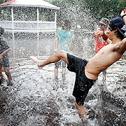 Payton Stuberg, 16, of Beaufort, right, kicks water towards Isaiah Jones, 13, of Beaufort, left, while in a foot of water outside the  Port Royal Skatepark on September 16, 2014.