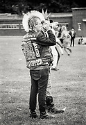 Two punks drinking on a playing field, UK, 1980s.