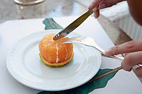 close up of hands cuting slice of an orange with knife and fork on a white plate