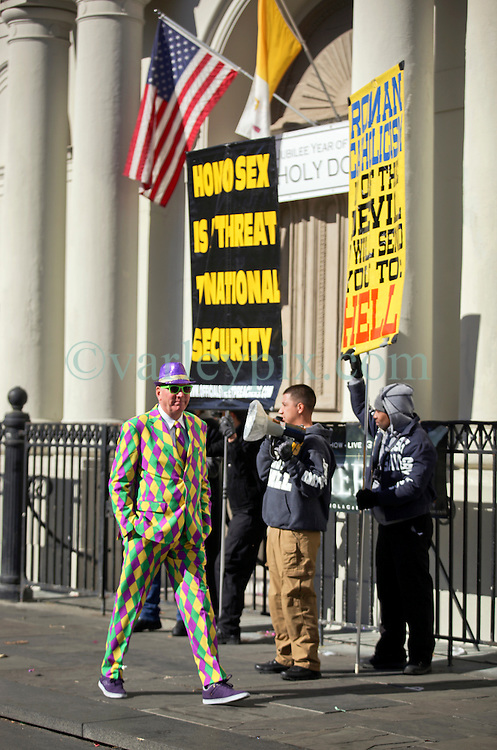 09 February 2016. New Orleans, Louisiana.<br /> Mardi Gras Day. Revelers dressed in bright costumes pass fundamentalist Christians spewing messages of hate outside St Louis Cathedral in the French Quarter. <br /> Photo©; Charlie Varley/varleypix.com