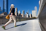 A pedestrian walks the Nichols Bridgeway with the Skyline of Chicago from Millennium Park in Chicago, IL, USA.