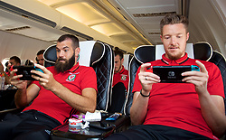 CARDIFF, WALES - Monday, September 4, 2017: Wales' Joe Ledley and goalkeeper Wayne Hennessey play Mario Kart on the Nintendo Switch on the team plane as the squad depart Cardiff Airport to travel to Chișinău ahead of the 2018 FIFA World Cup Qualifying Group D match against Moldova. (Pic by David Rawcliffe/Propaganda)