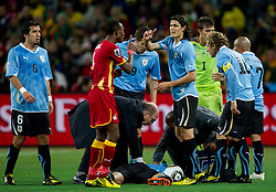 John Pantsil of Ghana in fight with  Edinson Cavani of Uruguay when Jorge Fucile of Uruguay was injured  during to the 2010 FIFA World Cup South Africa Quarter Finals football match between Uruguay and Ghana on July 02, 2010 at Soccer City Stadium in Sowetto, suburb of Johannesburg. (Photo by Vid Ponikvar / Sportida)
