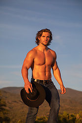 shirtless muscular cowboy outdoors on a mountain range at sunset