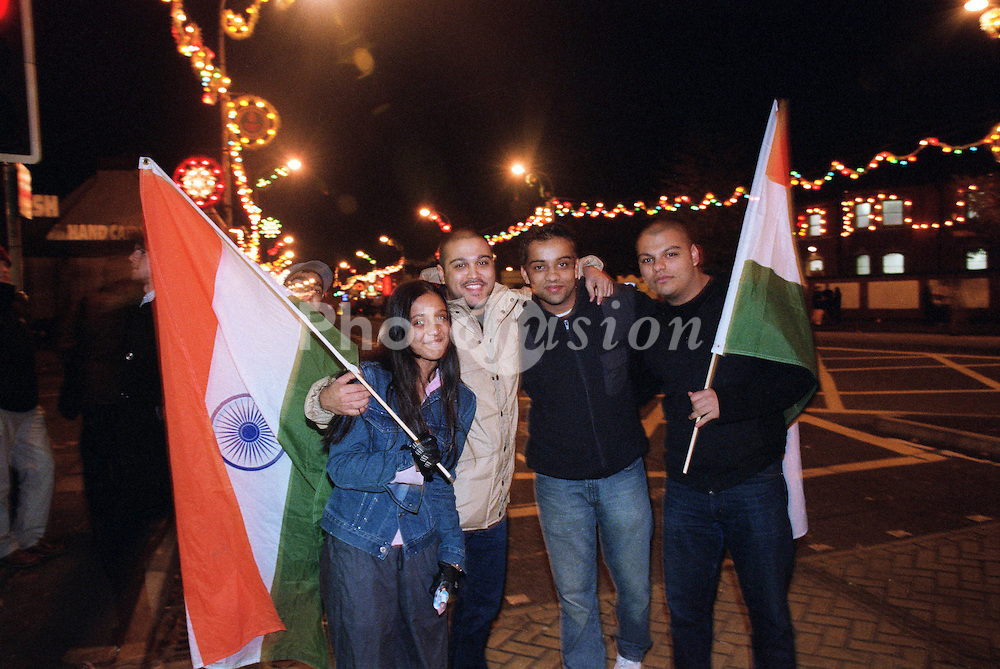 Group of young people standing together in street holding Indian flags to celebrate Diwali; festival of light,