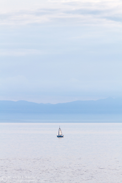 A small sailboat (a Hunter 280) in the Salish Sea (Georgia Straight) west of Vancouver.  Photographed from Juniper Point at  Lighthouse Park in West Vancouver, British Columbia, Canada. The mountains in the background are located on Vancouver Island.
