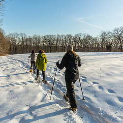 Three women snowshoeing in a field on Indian Hill in West Newbury, Massachusetts.