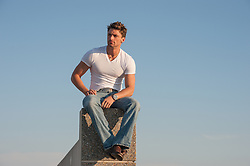 handsome man sitting on a rooftop against the sky