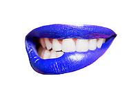 Close-up of teeth biting blue lip over white background