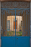 Close-up of ornate blue doors leading to a courtyard in Arles, France.