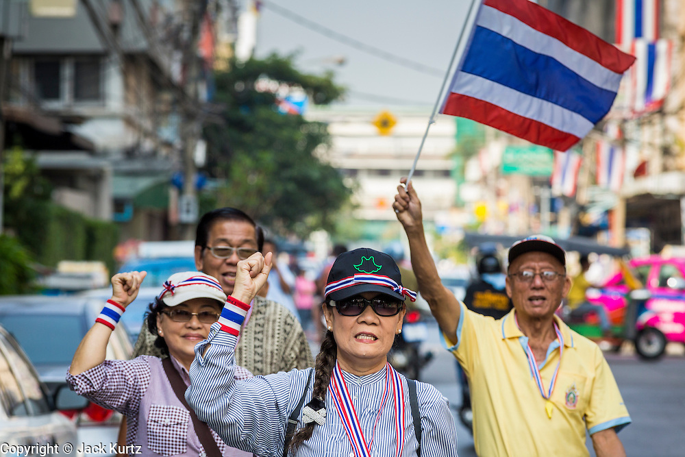"05 JANUARY 2014 - BANGKOK, THAILAND:  Anti-government protestors waving Thai flags and wearing ""Long Live the King"" headbands walk through Bangkok. Suthep Thaugsuband, leader of the anti-government protests in Bangkok, led the protestors on a march through the Chinatown district of Bangkok. Tens of thousands of people waving Thai flags and blowing whistles gridlocked what was already one of the most congested parts of the city. The march was intended to be a warm up to their plan by protestors to completely shut down Bangkok starting Jan. 13.    PHOTO BY JACK KURTZ"