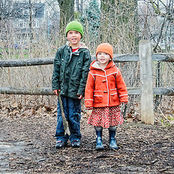 Two children, brother and sister, stand together wearing matching hats