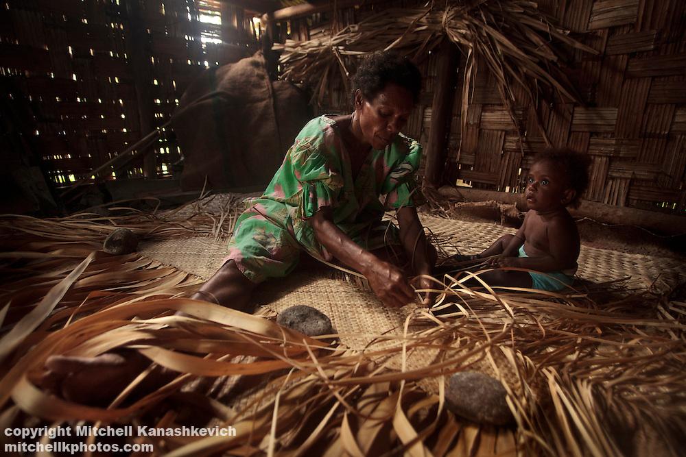 Ni Vanuatu woman weaving a traditional mat as a child watches in a hut in the village of Wintua, South West Bay, Malekula, Vanuatu