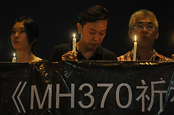 Malaysians hold candles during a vigil for the missing Malaysia Airlines passengers in Kuala Lumpur,  Malaysia, March 10, 2014. Malaysia Airlines flight MH370 with 239 people on board went missing early 08 March 2014 while on its way to Beijing, China. Malaysia will expand search and rescue operations to locate the missing Malaysia Airlines passenger jet with 239 people on board, as the third day of searching yielded no results, a senior Malaysian aviation official said,  Monday, 10th March 2014. Picture by Mohd FIrdaus / i-Images