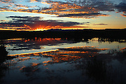 Still morning water adds to natures' palette for a firery orange sunrise over the mountains of Colorado.