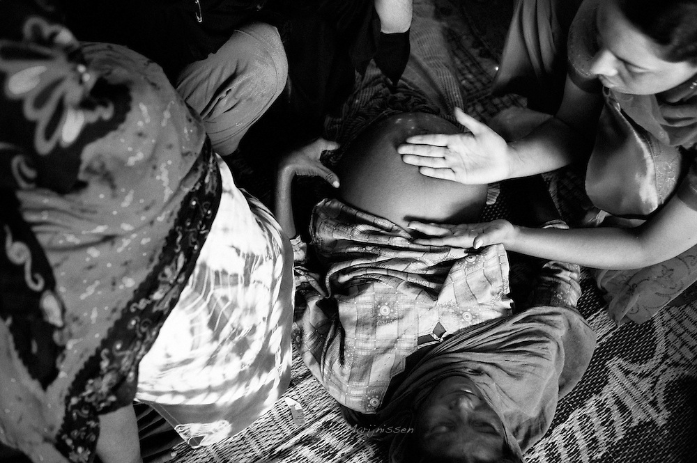 A midwife stationed in the tent camp checks the position and growth of a pregnant woman's baby. Trained staff provide care during the day and perform checks in the tents. In case of complications the patients get reffered to a nearby hospital for free care. Karachi, Pakistan, 2010
