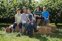Parents with three children (3-6) sitting on hay bales near orchard portrait