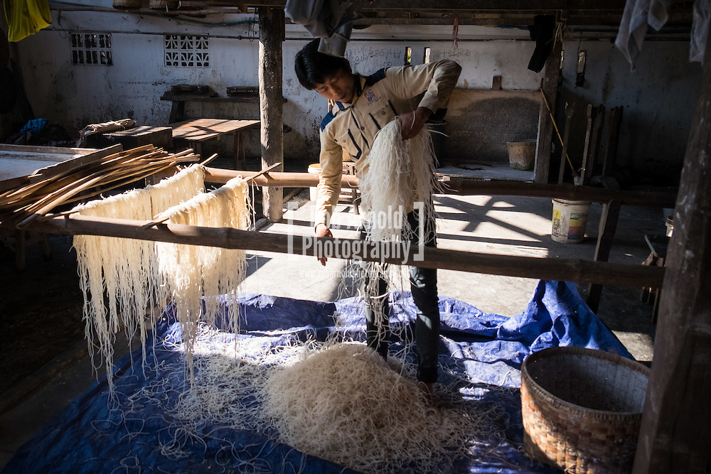 A man hanging freshly made rice noodles at a small factory in Hsipaw, Myanmar.