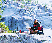 A middle aged man cooking outdoors in a high alpine environment.