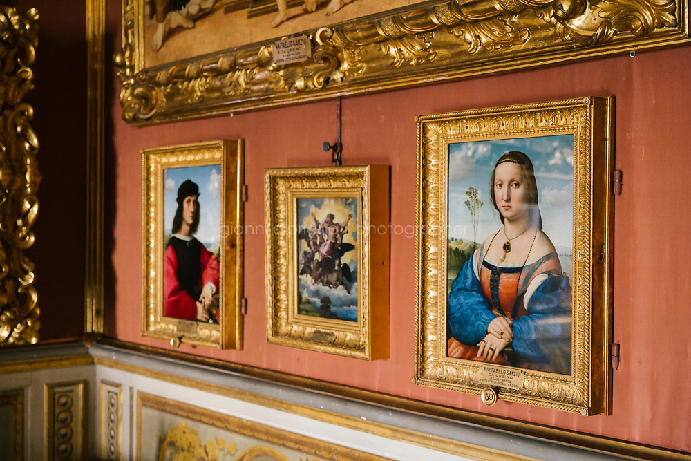 FLORENCE, ITALY - 3 JUNE 2018:  The dual portraits of Agnolo Doni and his wife Maddalena Strozzi, painted by Raphael round 1504-1505, are seen here in the Hall of Saturn of Palazzo Pitti before the paintings will be relocated in room 41 of the Uffizi, in Florence, Italy, on June 3rd 2018.<br /> <br /> As of Monday June 4th 2018, Room 41 or the &ldquo;Raphael and Michelangelo room&rdquo; of the Uffizi is part of the rearrangement of the museum's collection that has<br /> been defining Uffizi Director Eike Schmidt&rsquo;s grander vision for the Florentine museum.<br /> Next month, the museum&rsquo;s Leonardo three paintings will be installed in a<br /> nearby room. Together, these artists capture &ldquo;a magic moment in the<br /> first decade of the 16th century when Florence was the cultural and<br /> artistic center of the world,&rdquo; Mr. Schmidt said. Room 41 hosts, among other paintings, the dual portraits of Agnolo Doni and his wife Maddalena Strozzi painted by Raphael round 1504-1505, and the &ldquo;Holy Family&rdquo;, that Michelangelo painted for the Doni couple a year later, known as the<br /> Doni Tondo.