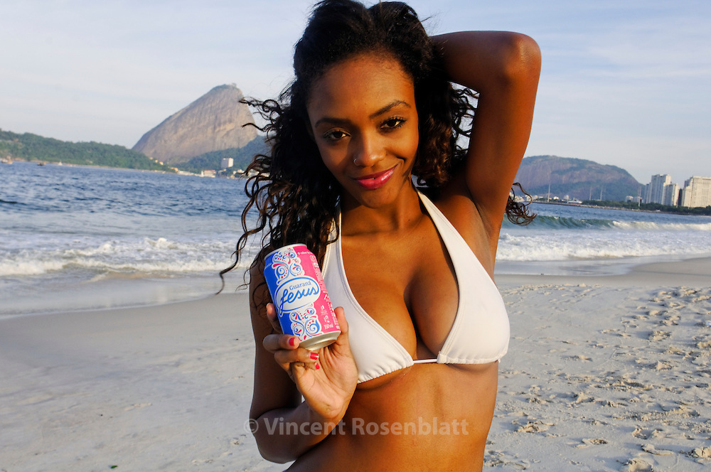 """Suellen, Rio de Janeirol model, tastes Jesus on the Flamengo beach..Guaraná Jesus is a Brazilian pink soft drink created in 1920 but now produced by a Coca-Cola bottler based in São Luís.  The drink is extremely popular within the region, reportedly outselling Coca-Cola, and is made from extracts of the guarana plant, which contains caffeine (sometimes called """"guaranine"""") and taste a mix of exotic fruit bubble gum & cinnamon.."""