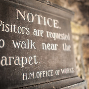 A sign warning visitors to walk near the parapet at Caernarfon Castle in northwest Wales. A castle originally stood on the site dating back to the late 11th century, but in the late 13th century King Edward I commissioned a new structure that stands to this day. It has distinctive towers and is one of the best preserved of the series of castles Edward I commissioned.