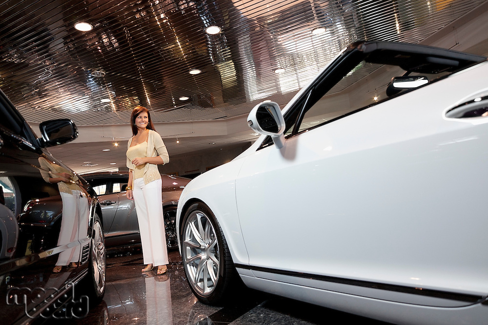 Full-length of smiling woman standing in car showroom