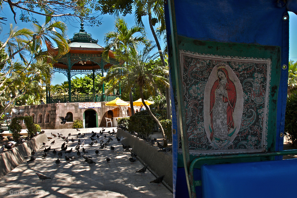 View of the main square of Mazatlan in Mexico,  and an image of the Guadalupe Virgin posted in the bak of a car