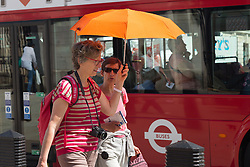 © Licensed to London News Pictures. 19/05/2014. London, UK. Two women shelter from the hot sun under an umbrella whilst walking in the sunshine near Westminster, London on 19th May 2014. Photo credit : Vickie Flores/LNP