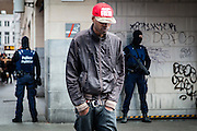Brussels 23 March 2016.Police officers guard the metro entrance of De Brouckere. A shabby guy with red cap passes by