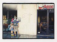 Proteste contro il summit del G8, Genova luglio 2001. Corteo di sabato 21 luglio. Piazzale Kennedy. Una coppia di manifestanti legge un manifesto affisso sul muro di un'attività commerciale devastata il giorno prima dal cosiddetto Black Block. Immediatamente prima del corteo del sabato pomeriggio il Genoa Social Forum denuncia alla stampa la strategia di infiltrazione delle manifestazioni del venerdì da parte di elementi del Black Block, i quali avrebbero dato alle forze di polizia il pretesto per caricare anche i manifestanti pacifici.