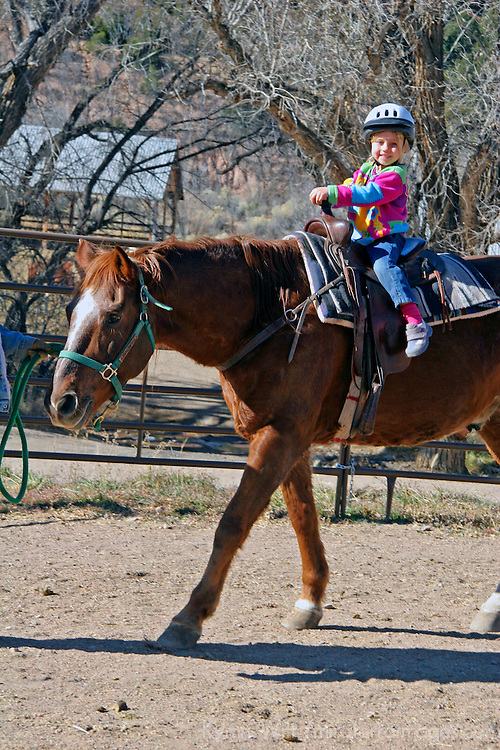 North America, USA, New Mexico. A young girl rides a horse in a ring at riding stables of Bishop's Lodge Resort near Santa Fe, New Mexico.