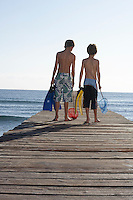 Two boys (6-11) walking on jetty carrying fishing nets and swim fins back view