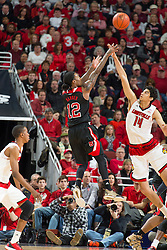 North Carolina State guard Anthony Barber, left, has his shot contested by Louisville forward Anas Mahmoud. <br /> <br /> The University of Louisville hosted the North Carolina State, Saturday, Feb. 14, 2015 at the Yum Center in Louisville. <br /> <br /> Photo by Jonathan Palmer