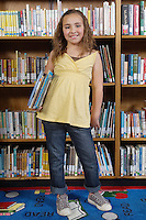 School girl holding books in library, portrait