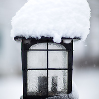 A pile of snow atop and pole light.